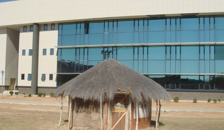 A thatch-roofed round hut directly in front of the Chinese-built glass block that is the Faculty of Business at the University of Botswana in Gaborone.