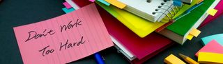 An image of colorful notebooks, pens and a post-it saying 'Don't work too much'.