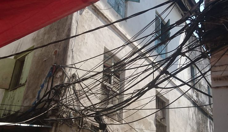 Bundles of electrical wires, assorted cables and water pipes attached to houses throughout the old kasbah city of Zanzibar.