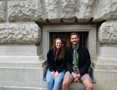 Two smiling students are sitting in front of the Albertina library.