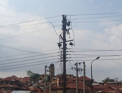 Electricity pole and cables photographed from below against the background of an urban neighbourhood in Ibadan, Nigeria.