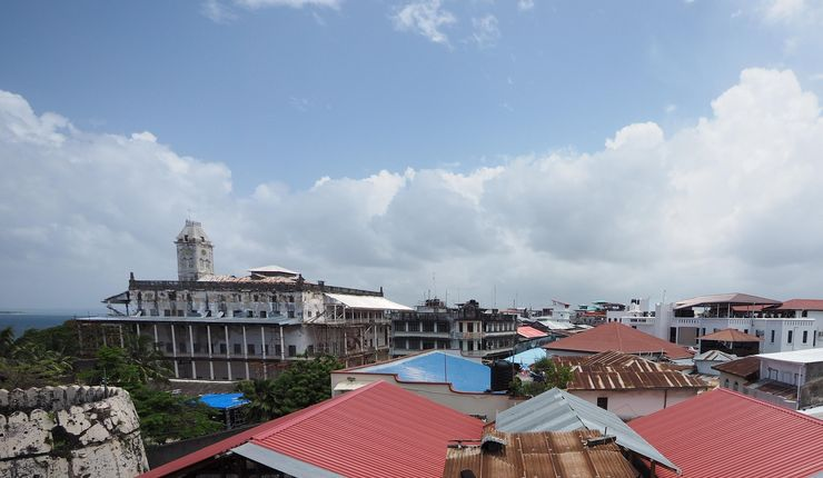A bird's eye view of the roofs of Zanzibar Stone Town, showing roofs made of different materials from brown, rusty corrogated iron to new, read, shiny plastic roofs.