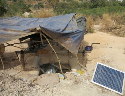 A mining pit in Burkina Faso that is covered with a tarp and connected to a solar panel.